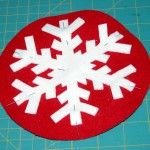 Fused double layer white wool applique pinned to the fused layers of red wool