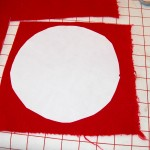 """Rough' cut fusible circle ironed to 1 layer of red wool background"