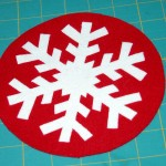 Single layer snowflake applique fused to 2 layer fused red wool background