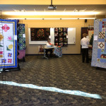 Another room of quilts as well as watchful member Pam Botton is doing applique!